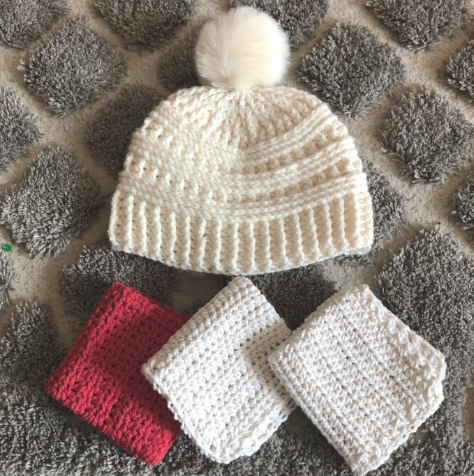 crochet white hat and three pieces of red and white crocheted cloth