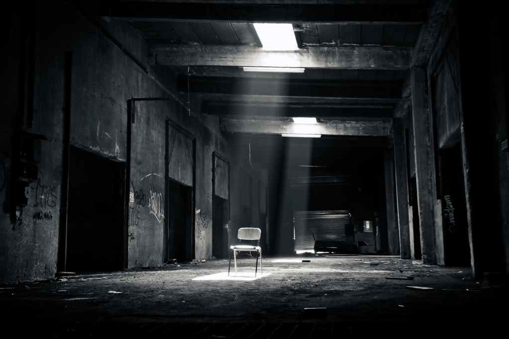 grayscale photo of chair inside the establishment; difference between paranormal and horror