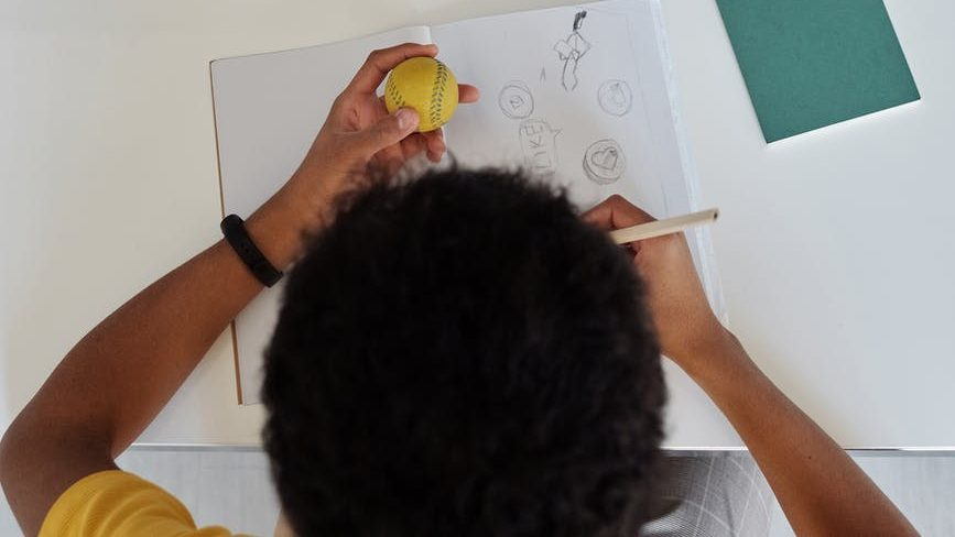 top view photo of boy drawing on white paper