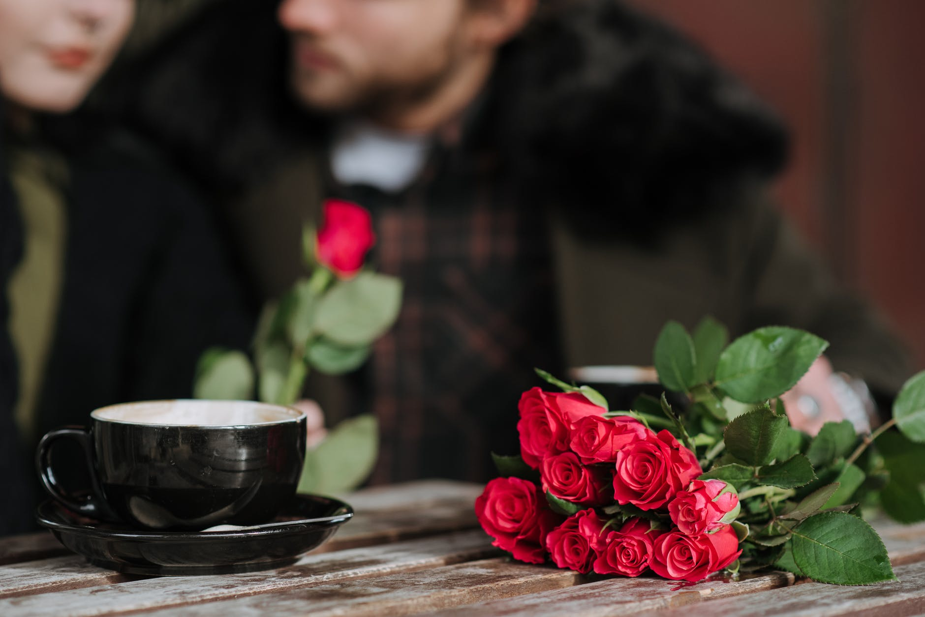 anonymous couple at cafe table with blooming roses and coffee