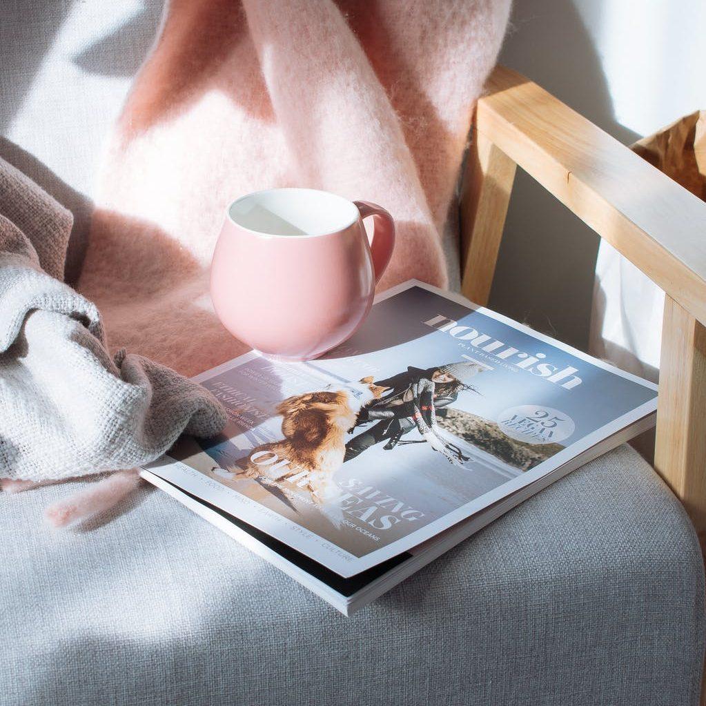 pink mug and magazine book