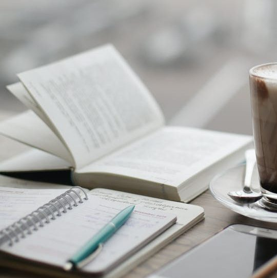warm coffee drink with open book and writing pad