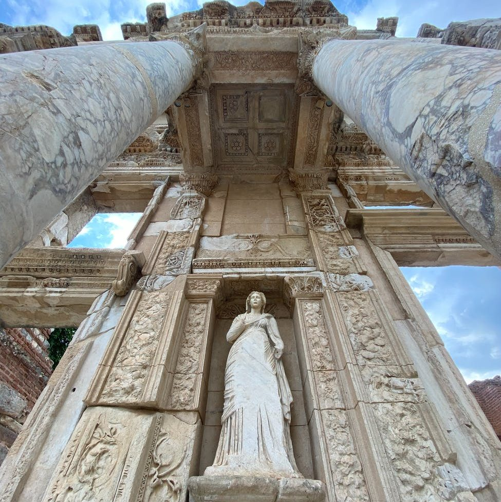 low angle photography of concrete building; goddess; god tempus