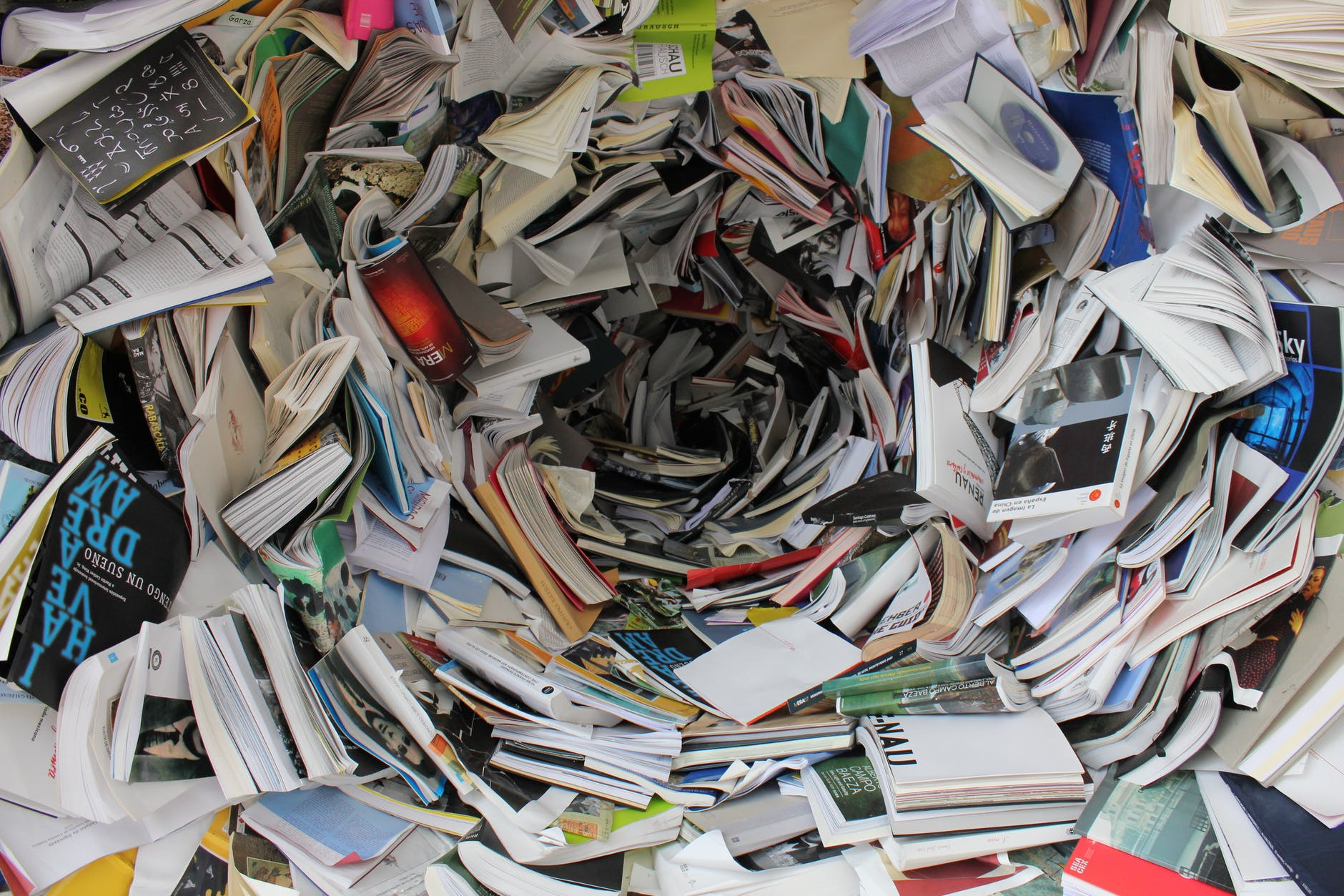 pile of covered books; Research, research, research; 8 Tips About World Building New Writers Should Know