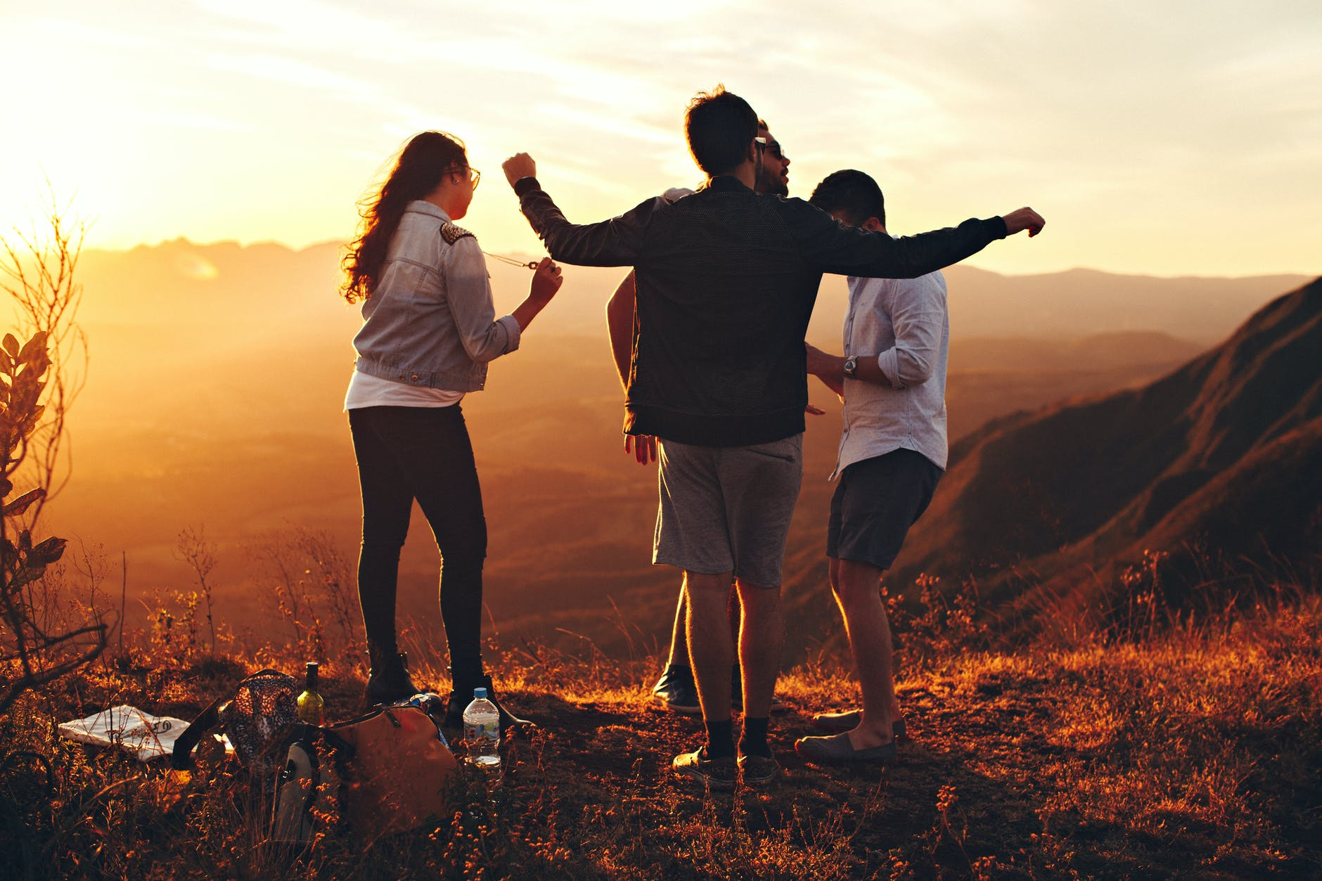 four person standing at top of grassy mountain; college roommates; first year students