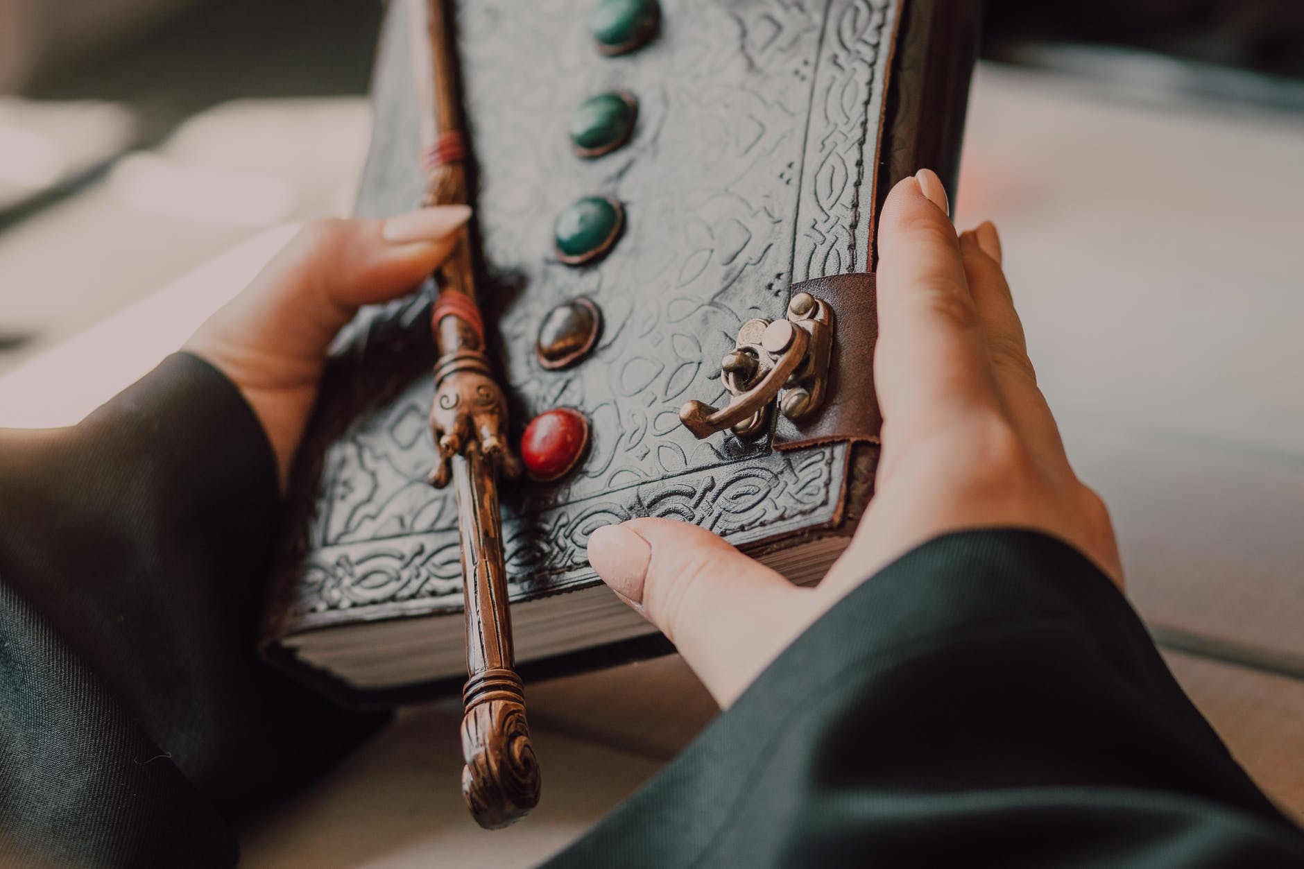 hands with medieval leather book and wand; fantasy books; author on writers week