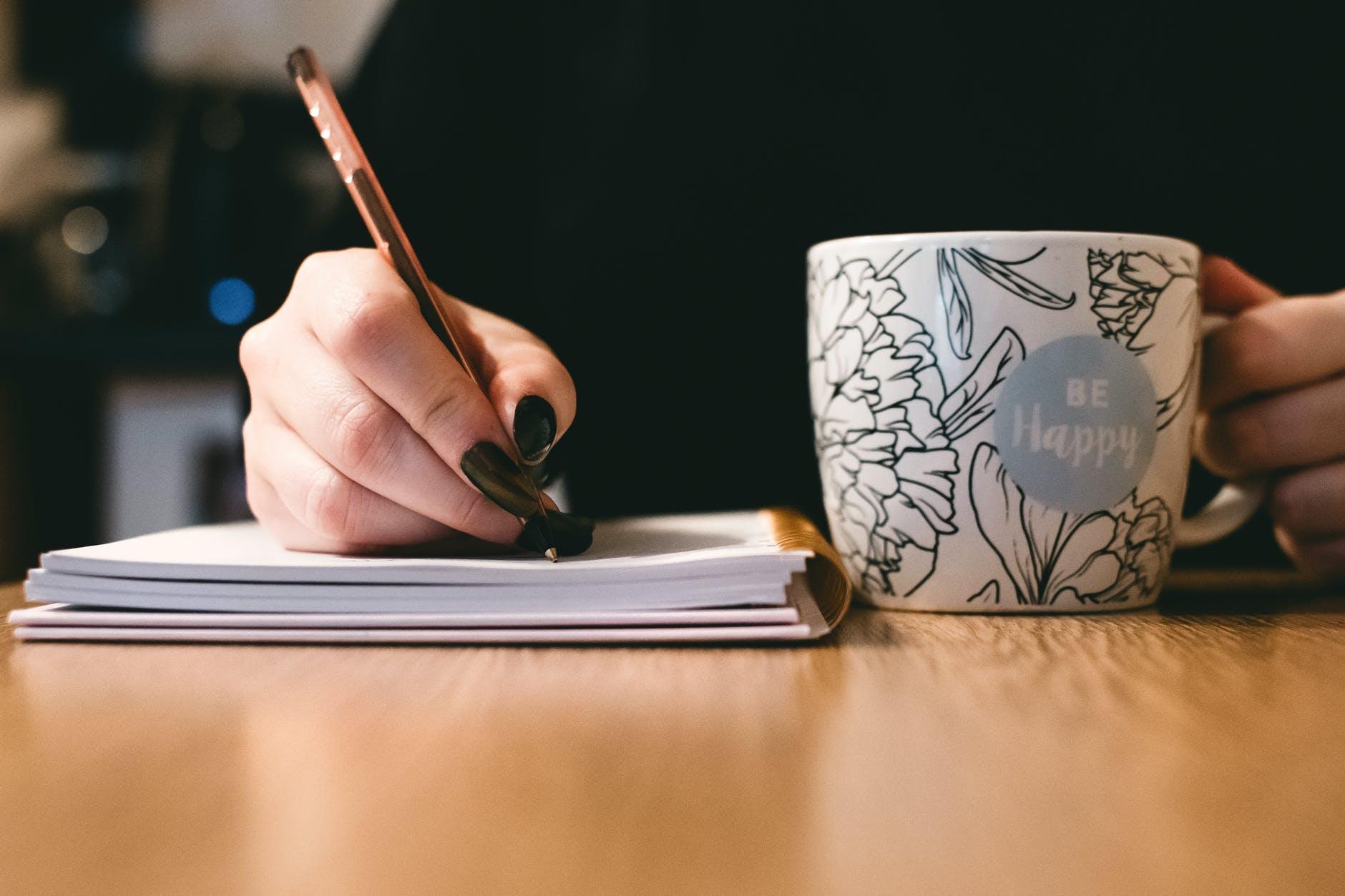 person holding white ceramci be happy painted mug; poetry;  C. L. Schneider Author Spotlight
