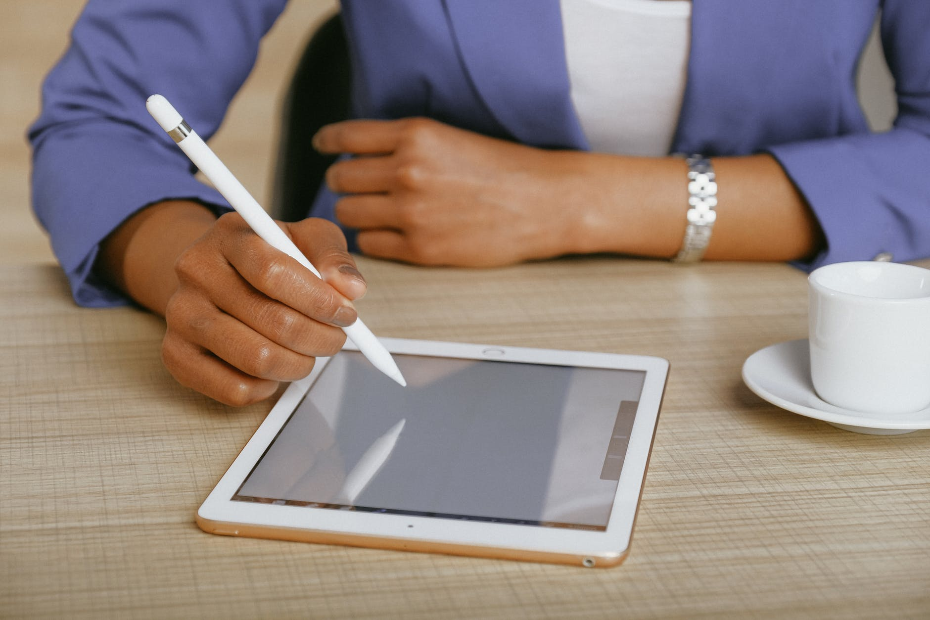 close up of woman using digital tablet to write; author spotlight with Winnie Tataw