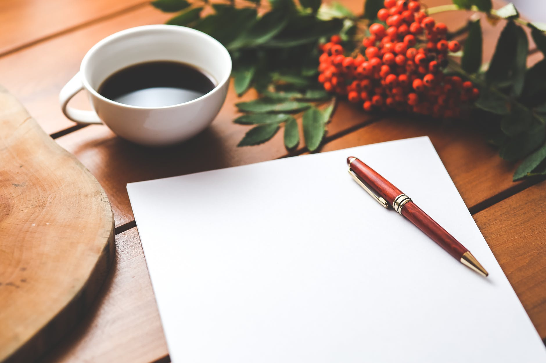 blank paper with pen and coffee cup on wood table