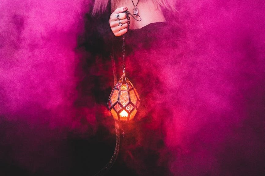 spooky witch with lamp in pink smoke; magic and fantasy